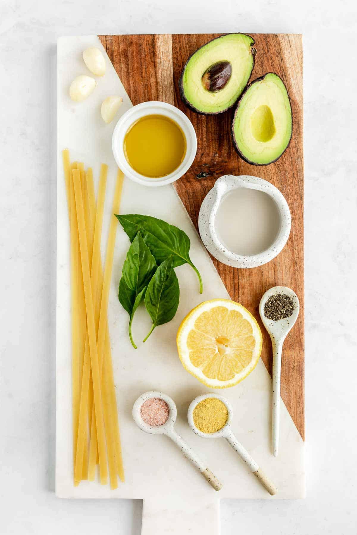 avocado, basil, garlic, olive oil, nutritional yeast, lemon juice, salt, pepper, and plant-based milk on a marble board