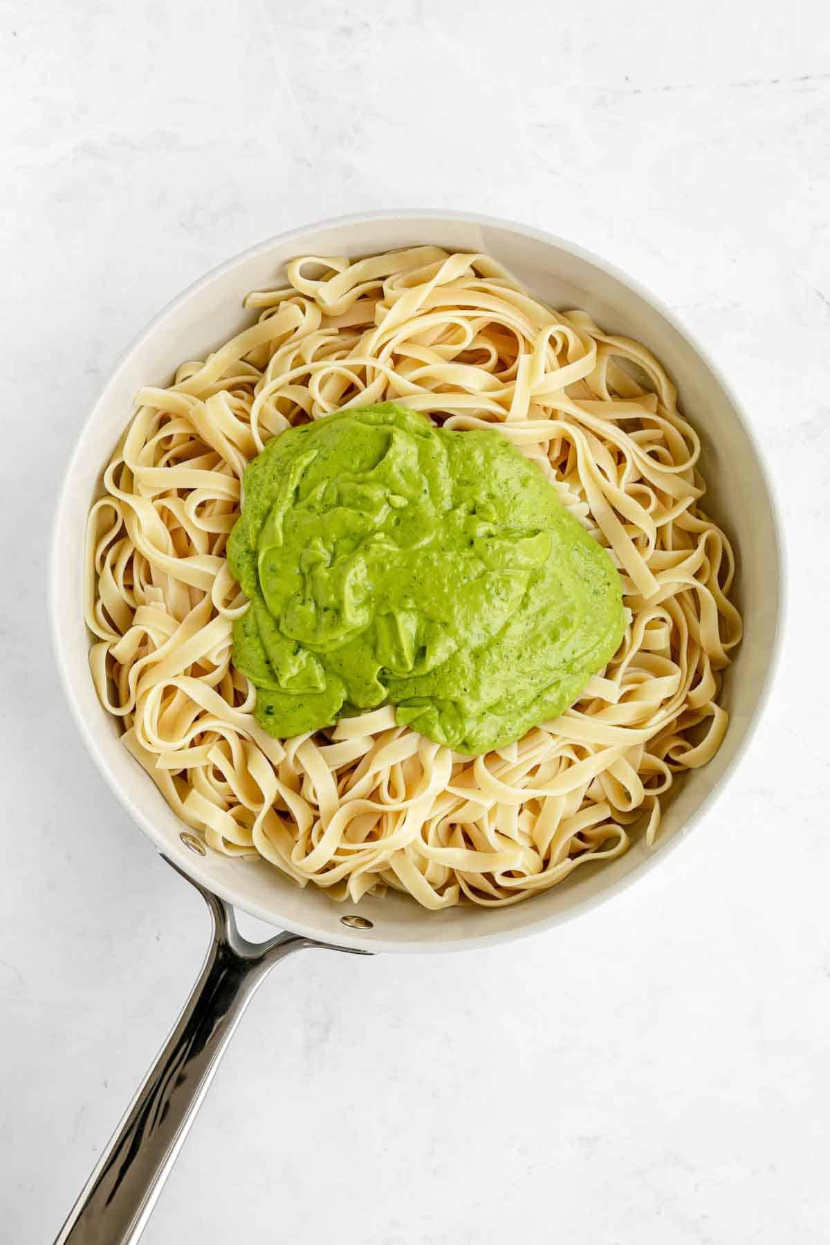 fettuccine pasta in a pot with avocado pesto sauce on top