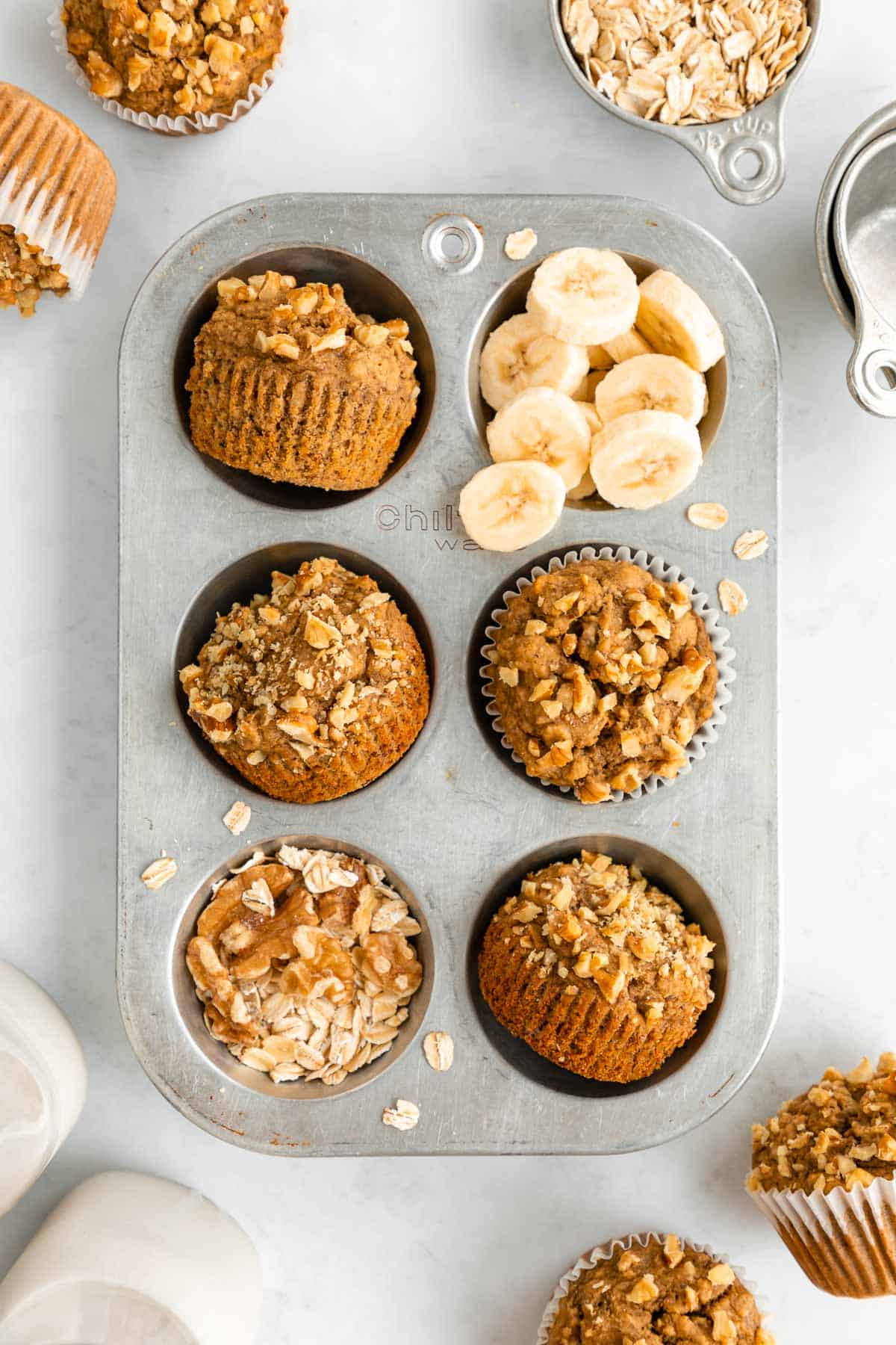 healthy banana nut muffins in a vintage muffin tin with walnuts, oats, and sliced banana