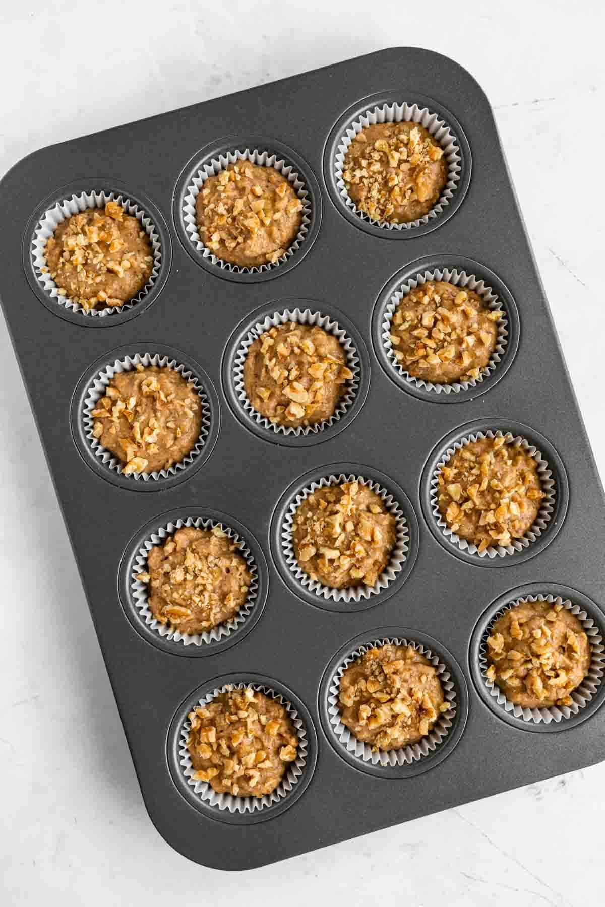 unbaked muffin batter inside a muffin tin