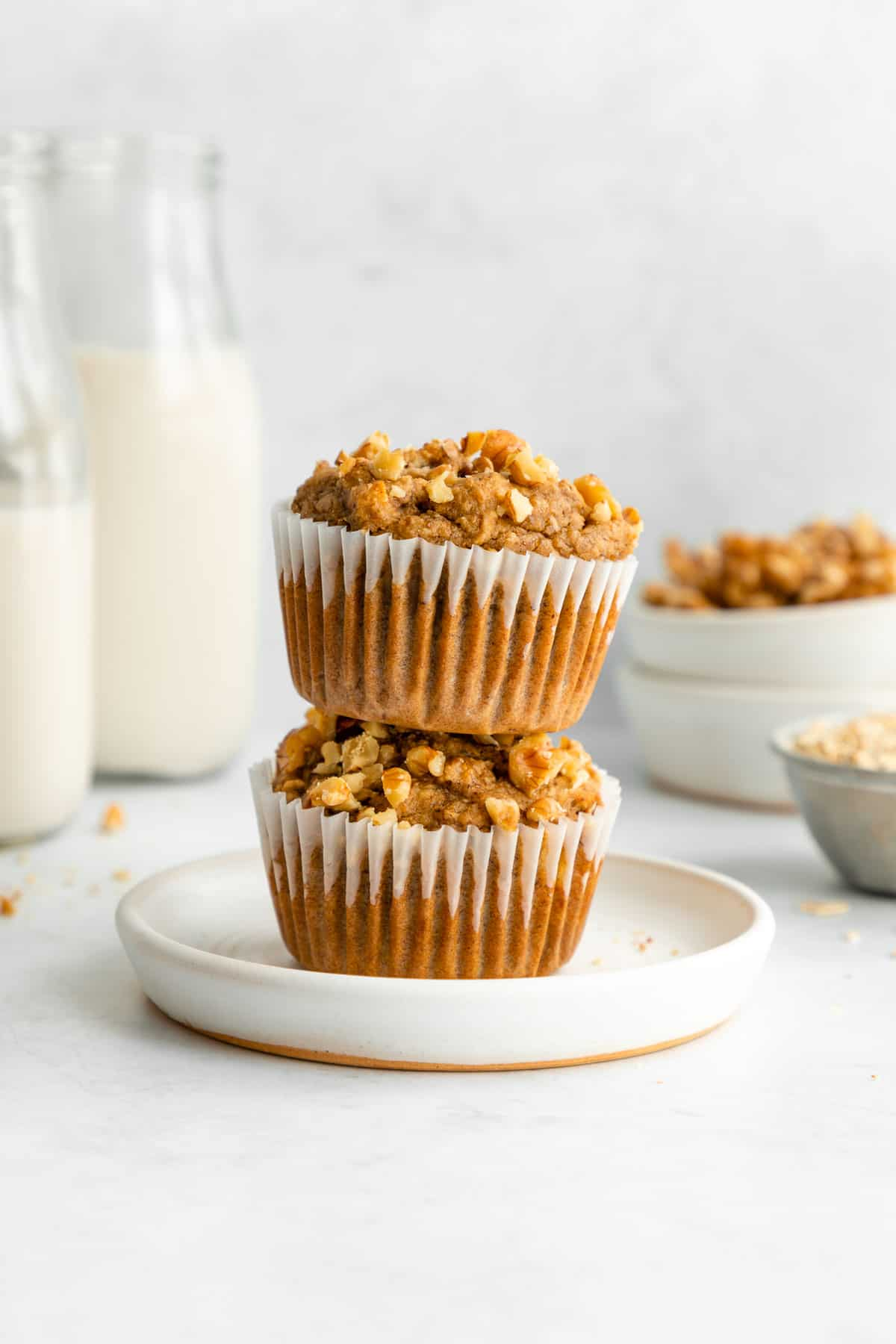 two healthy banana nut muffins stacked on a white plate beside glasses of almond milk