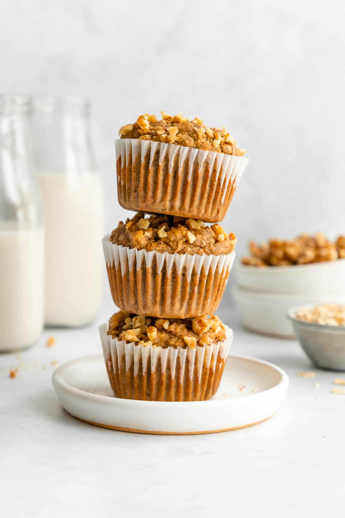 a stack of three vegan banana nut muffins on a white plate