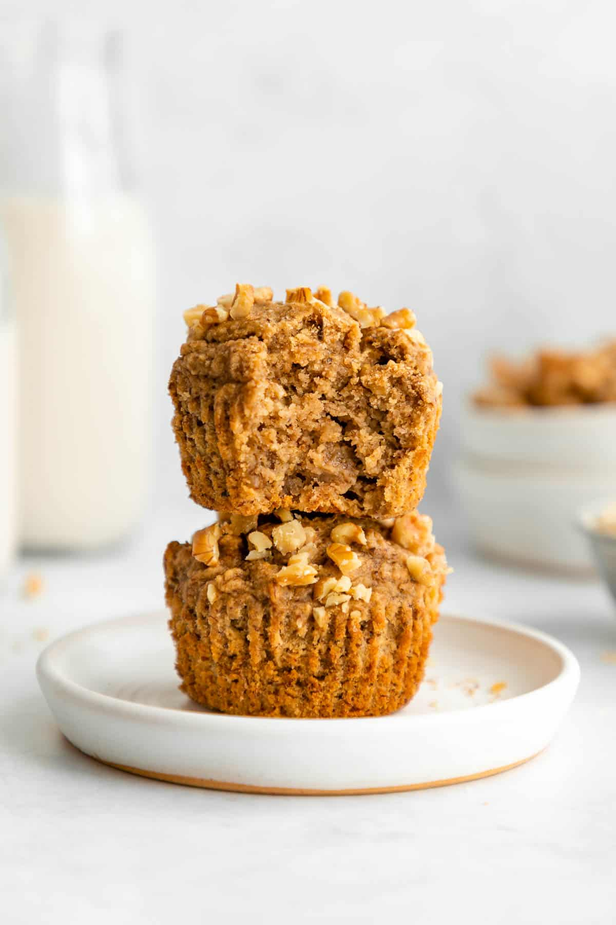 a stack of two vegan banana muffins on a white plate with a bite taken out of the top one
