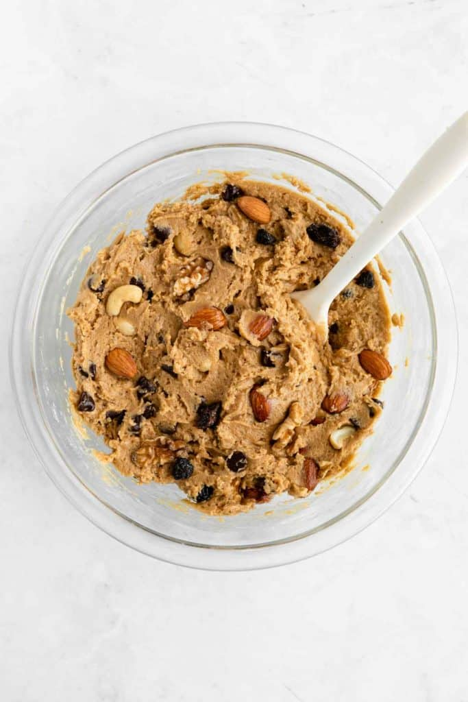 mixing fruit and nut cookie dough in a glass bowl