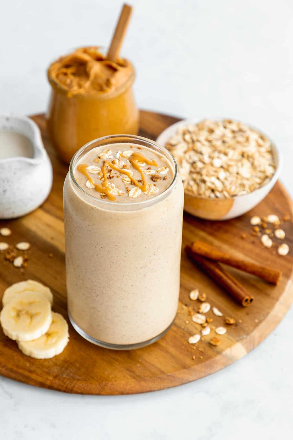 a peanut butter oatmeal smoothie bowl in a glass on top of a round wooden board