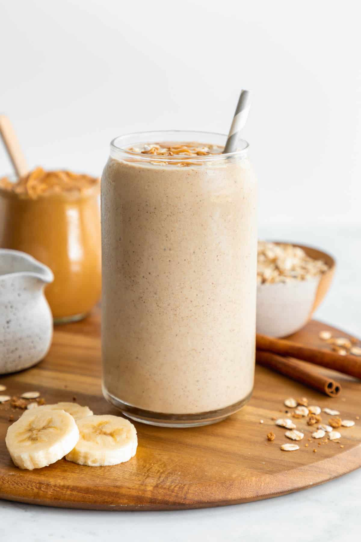 an oatmeal smoothie inside a glass surrounded by sliced banana, a jar of peanut butter, oats, and cinnamon sticks