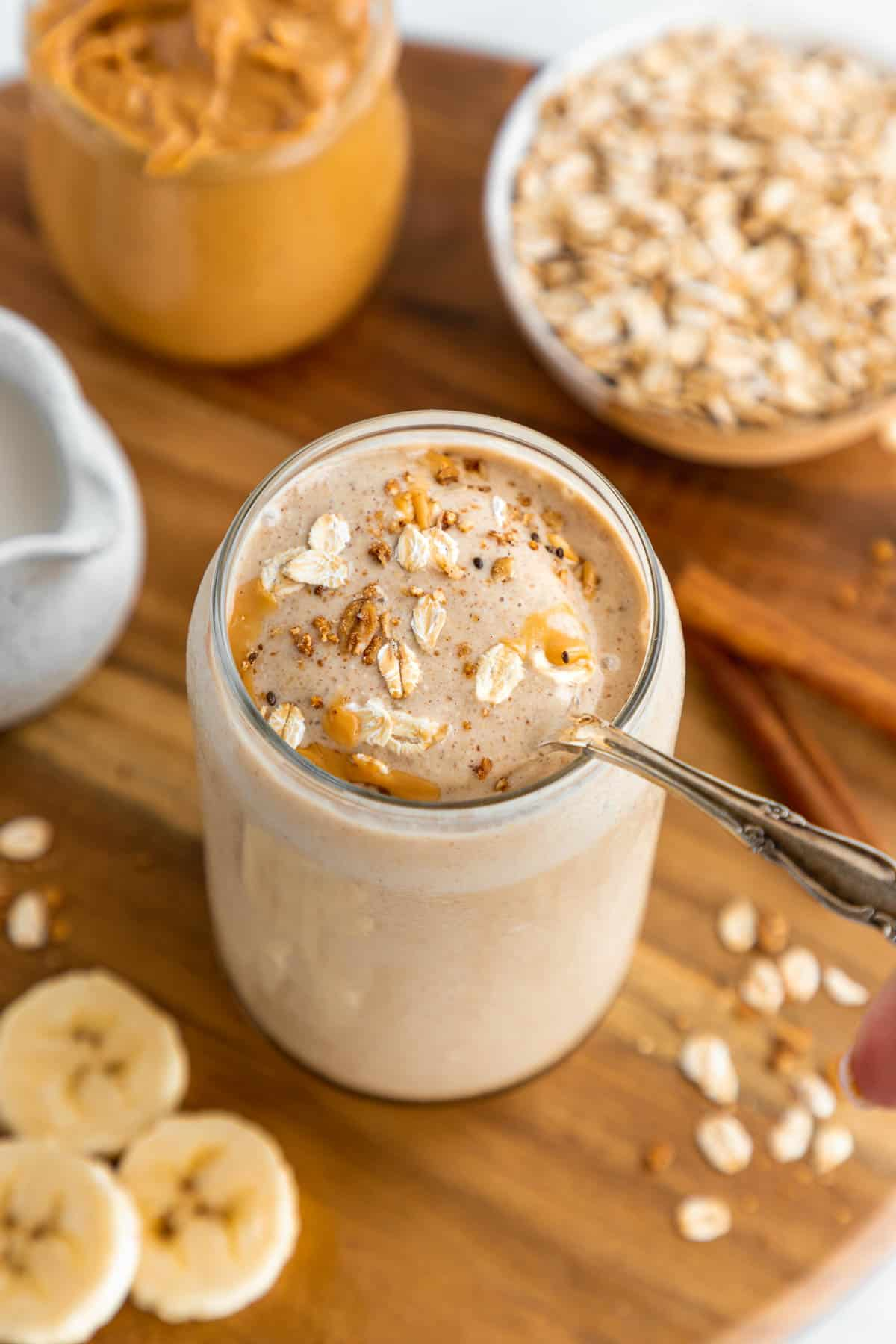 a spoon scooping into a peanut butter oatmeal smoothie inside a glass