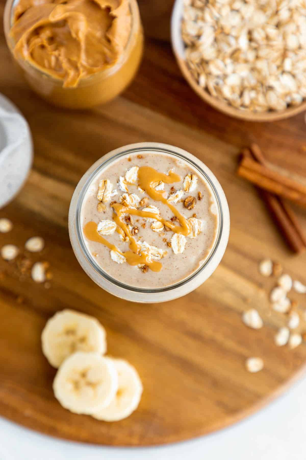 overhead photo of a peanut butter oatmeal smoothie inside a glass, surrounded by sliced banana, rolled oats, and oat milk