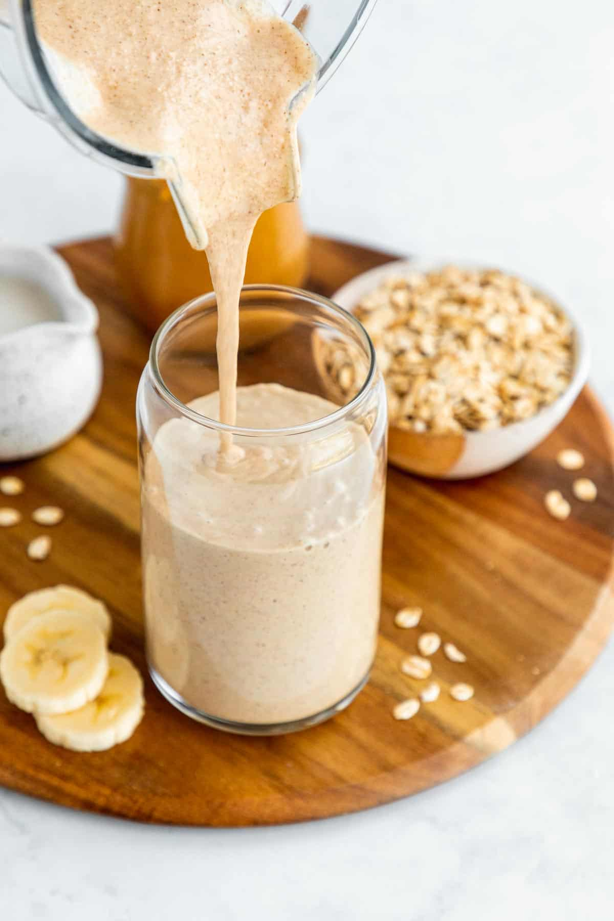 pouring an oatmeal smoothie into a glass out of a vitamix blender