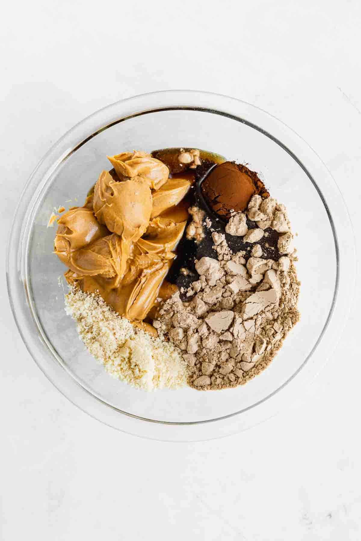 chocolate protein powder, peanut butter, almond flour, cocoa powder, and maple syrup in a glass bowl