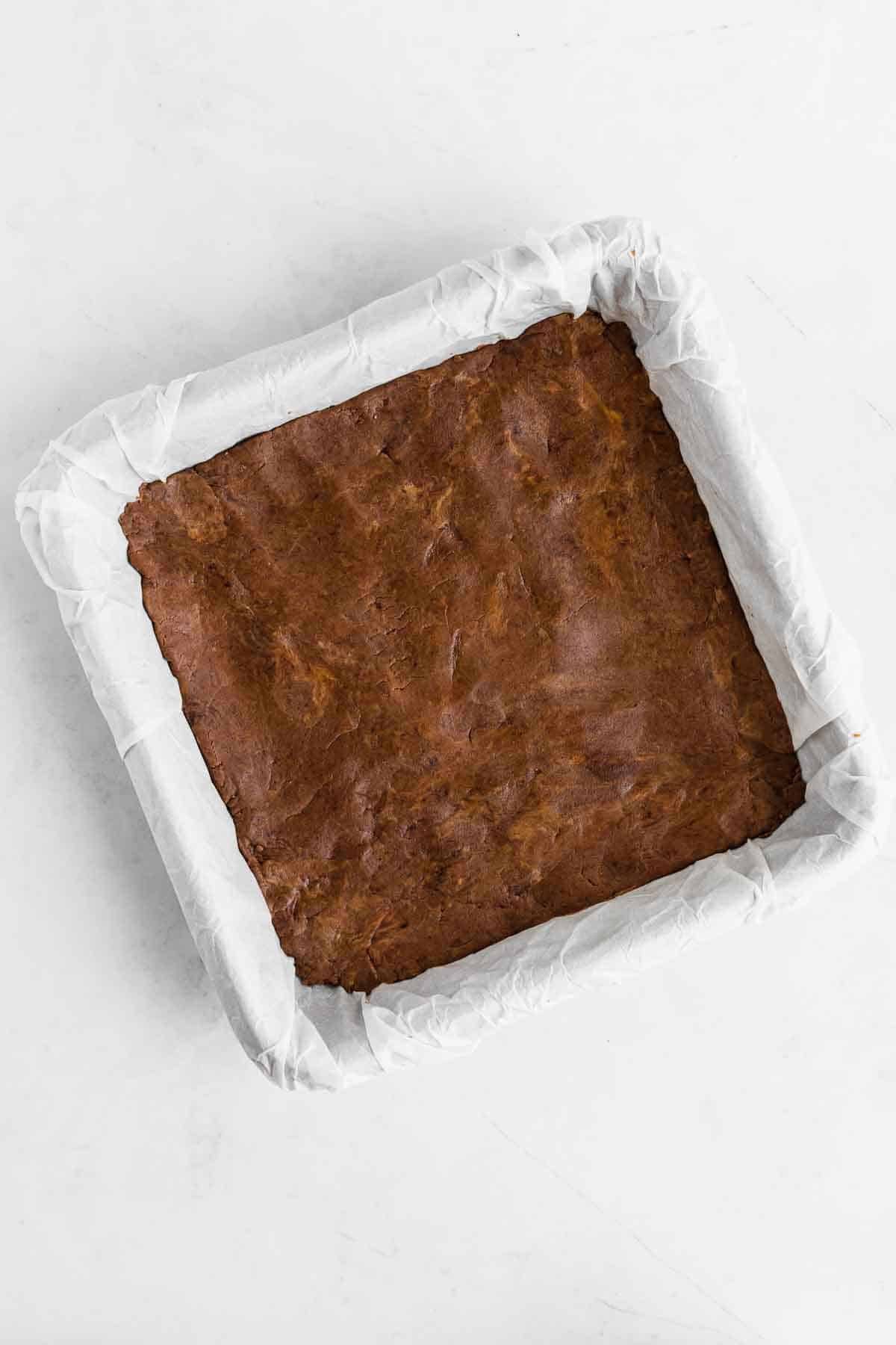chocolate protein bar dough pressed across the bottom of a square baking dish