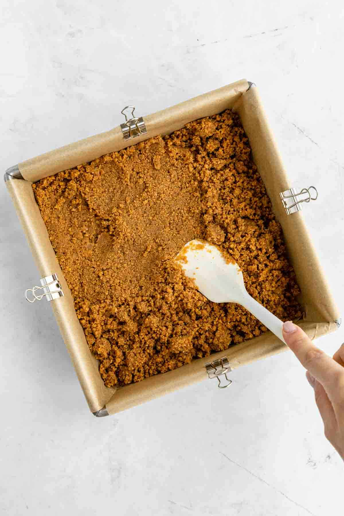 a spatula pressing graham cracker crust into a square baking dish