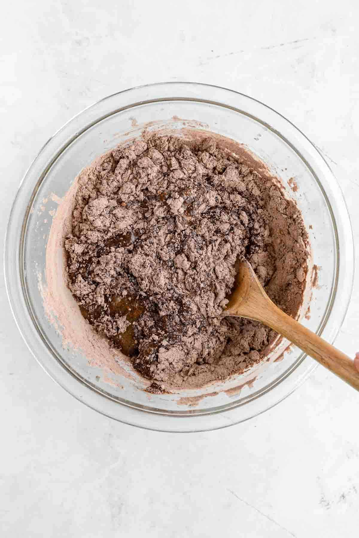 a wooden spoon mixing dry ingredients into wet ingredients for brownie batter