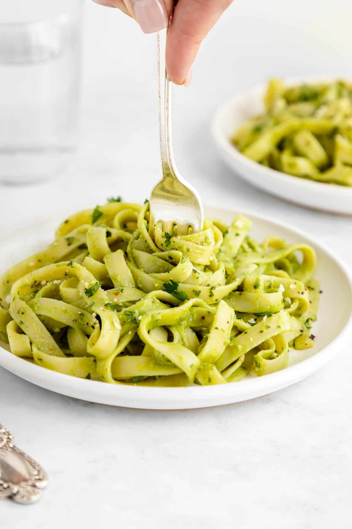 a fork twirling vegan avocado pasta on a white plate