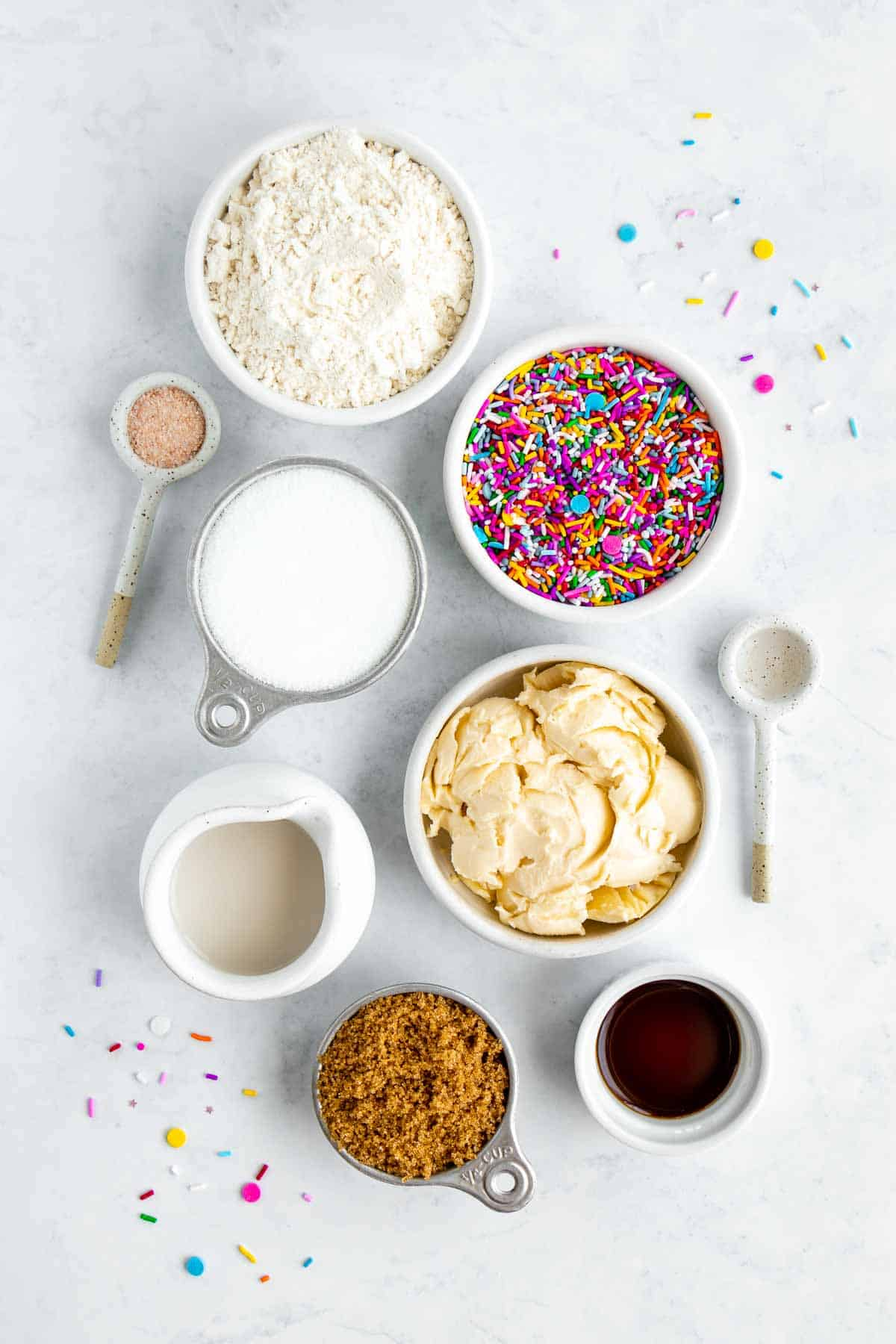 bowls filled with flour, rainbow sprinkles, vegan butter, brown sugar, white sugar, vanilla extract, almond extract, and almond milk