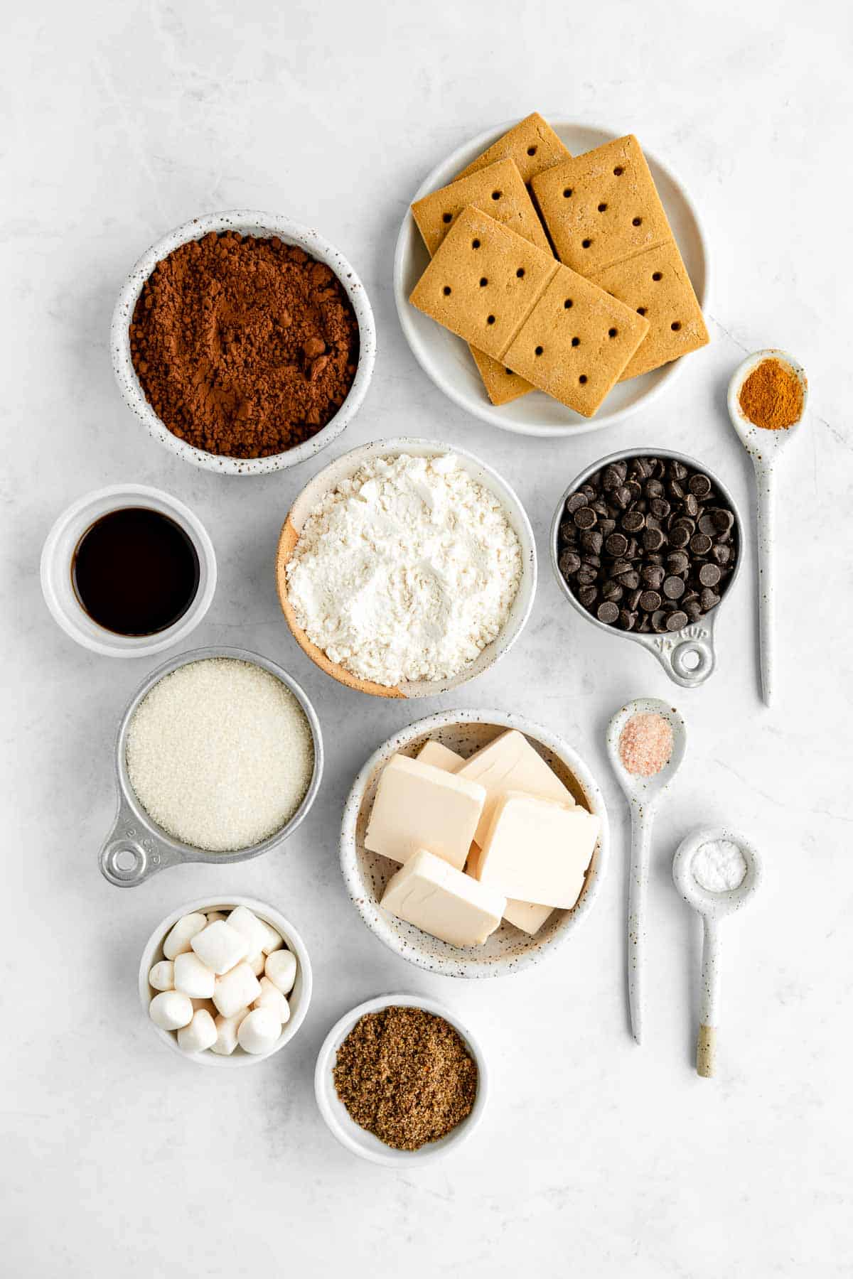 bowls filled with graham crackers, vegan marshmallows, chocolate chips, dairy-free butter, flour, sugar, cocoa powder, and vanilla