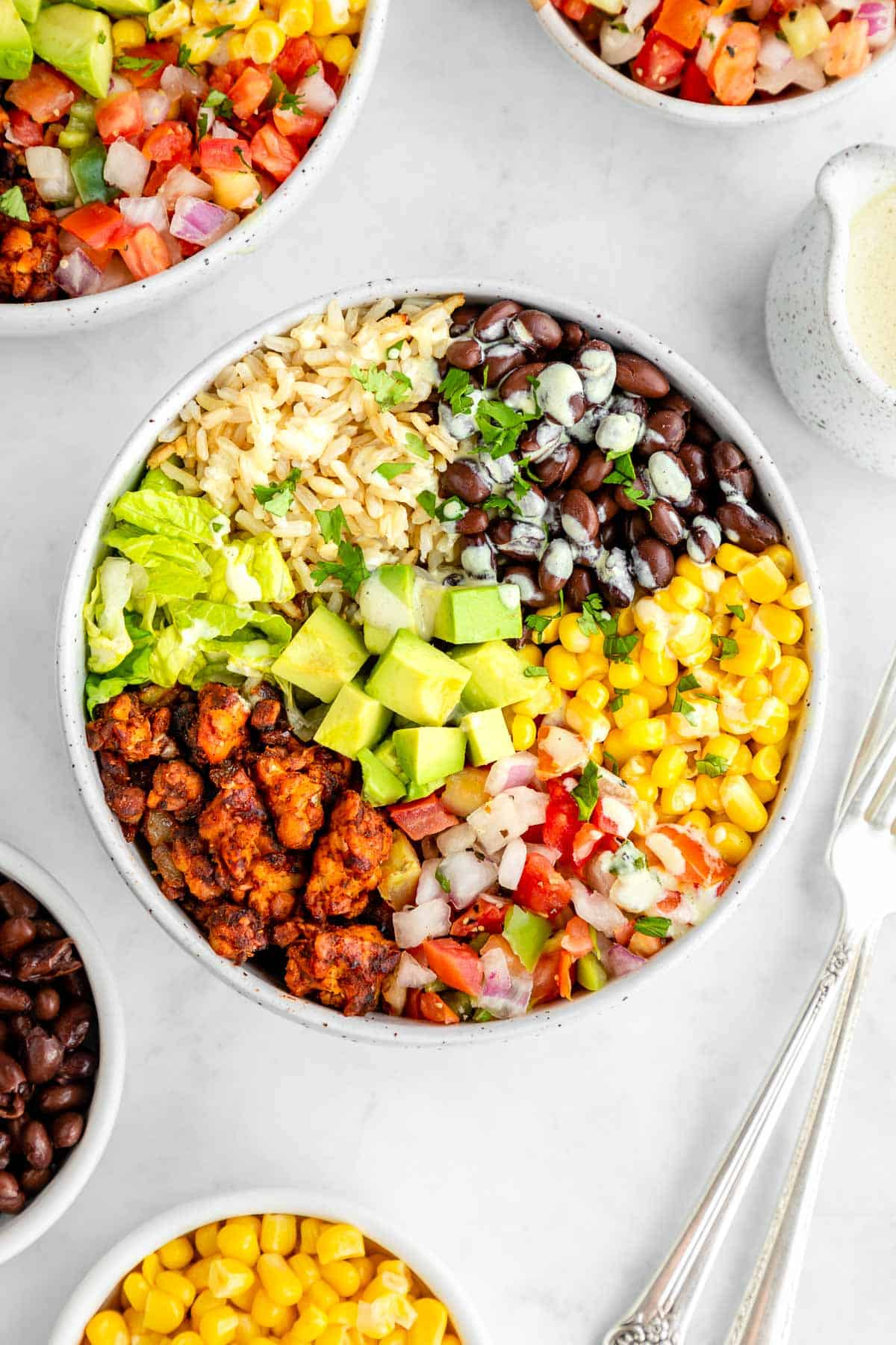 a vegan tempeh burrito bowl with black beans, corn, avocado, lettuce, and pico de gallo