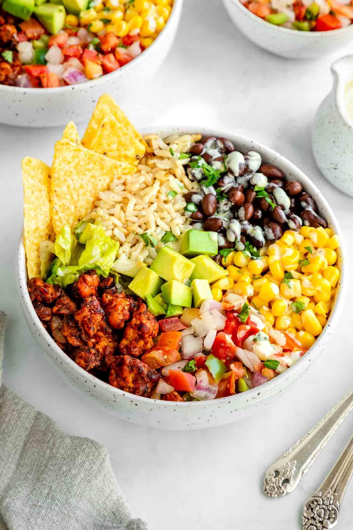 a vegan tempeh burrito bowl with corn tortilla chips on top