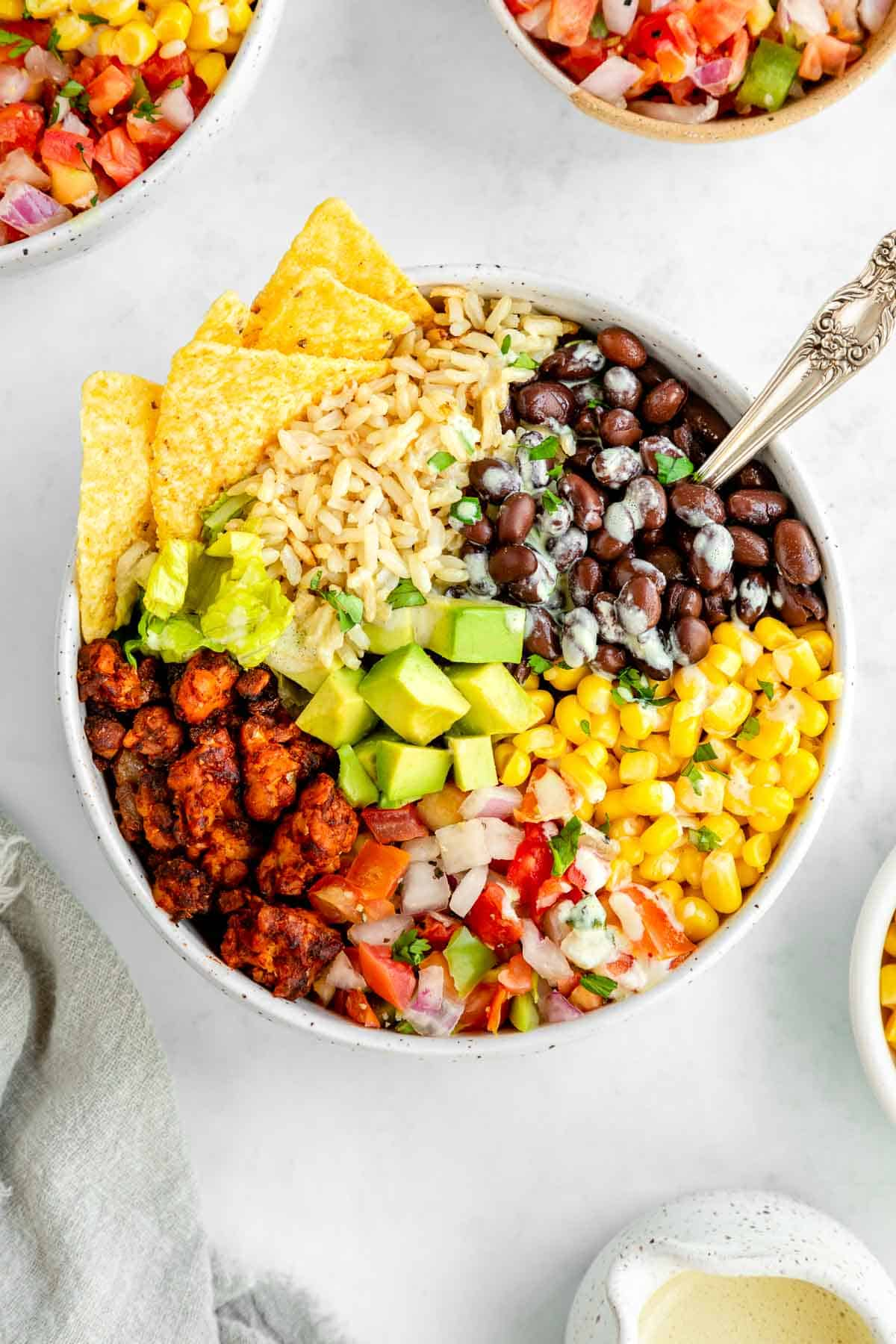 a vegan tempeh burrito bowl with a spoon sticking into it