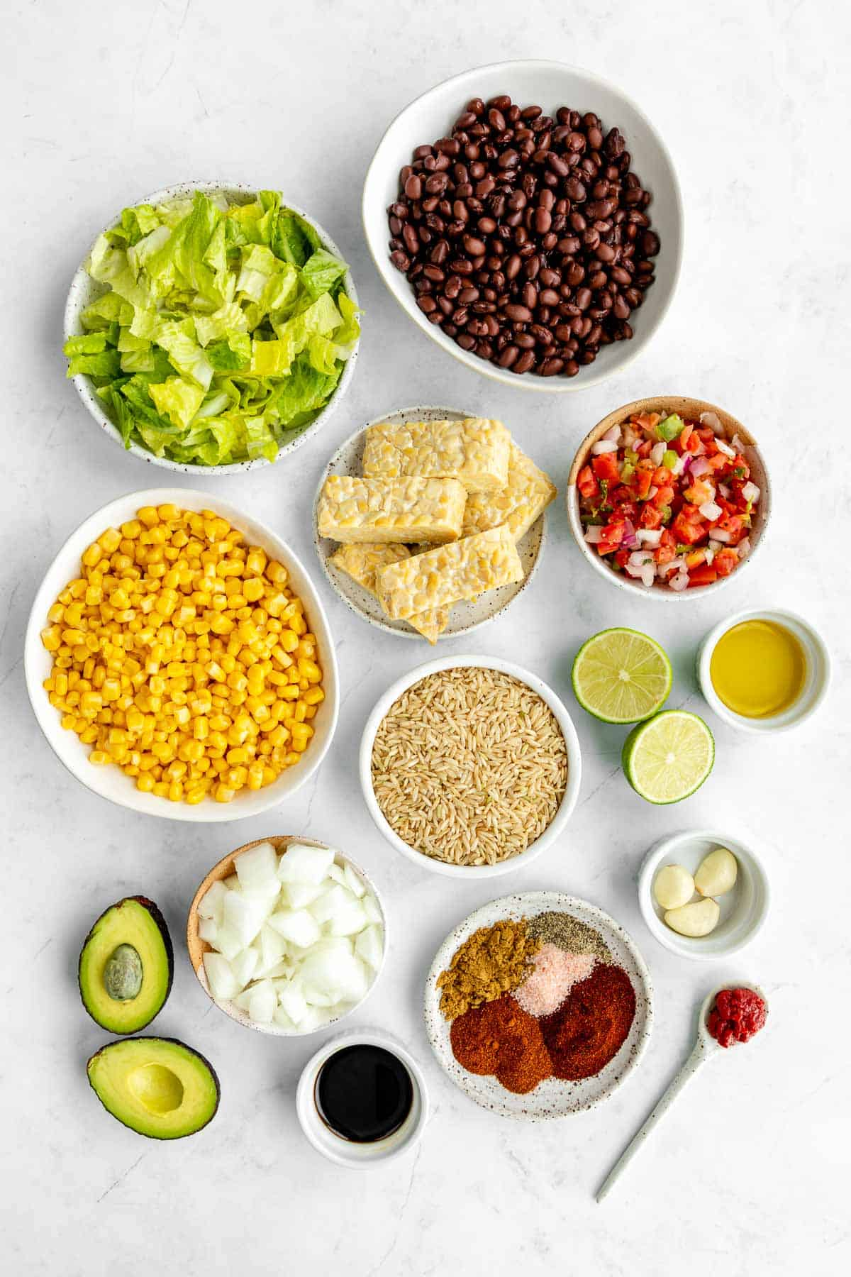 bowls of ingredients for a vegan tempeh burrito bowl, including corn, lettuce, black beans, pico de gallo, onion, avocado, and spices