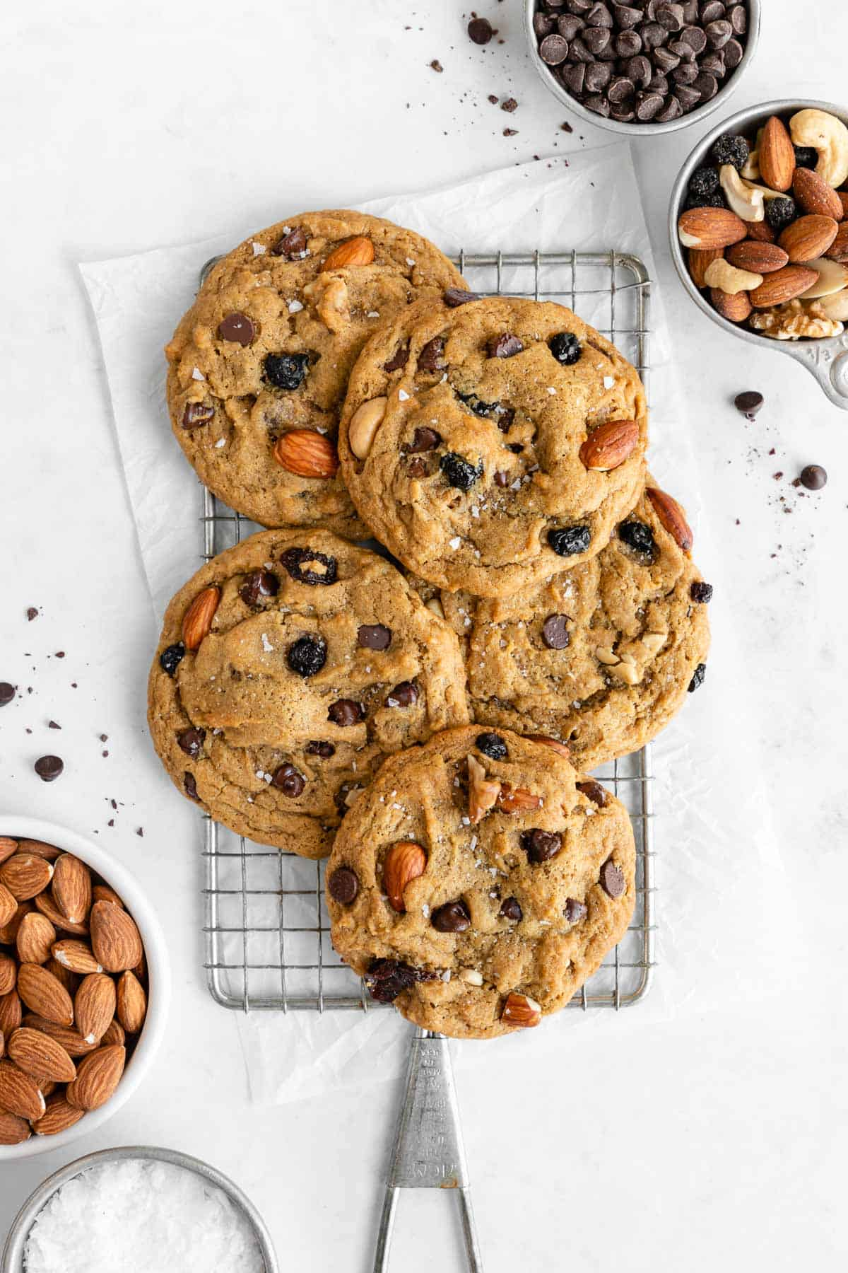 a pile of vegan trail mix cookies on a cooling rack surrounded by bowls of chocolate chips, nuts, and dried fruit