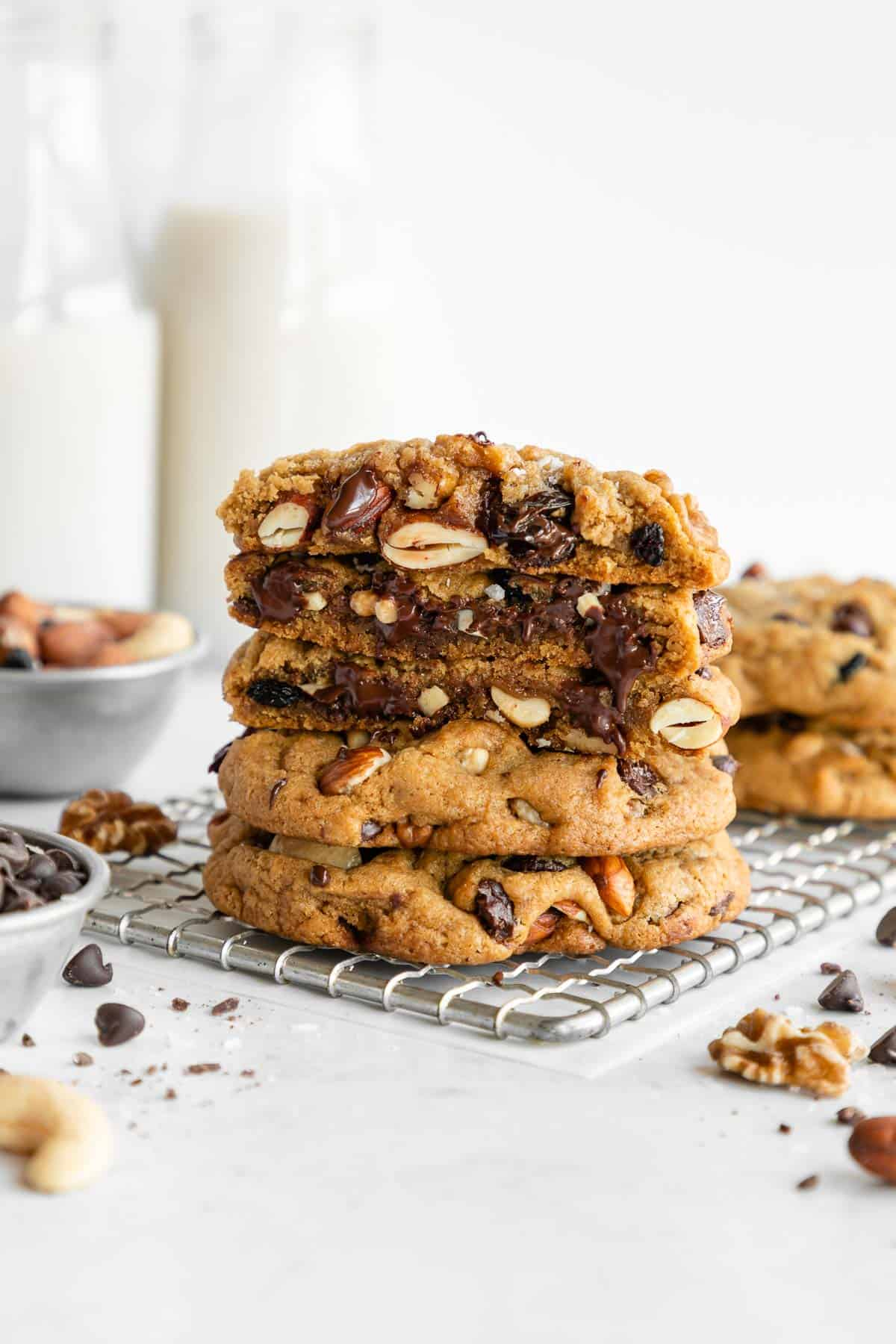 a stack of vegan trail mix cookies sliced in half on a cooling rack surrounded by chocolate chips, mixed nuts, and fruit