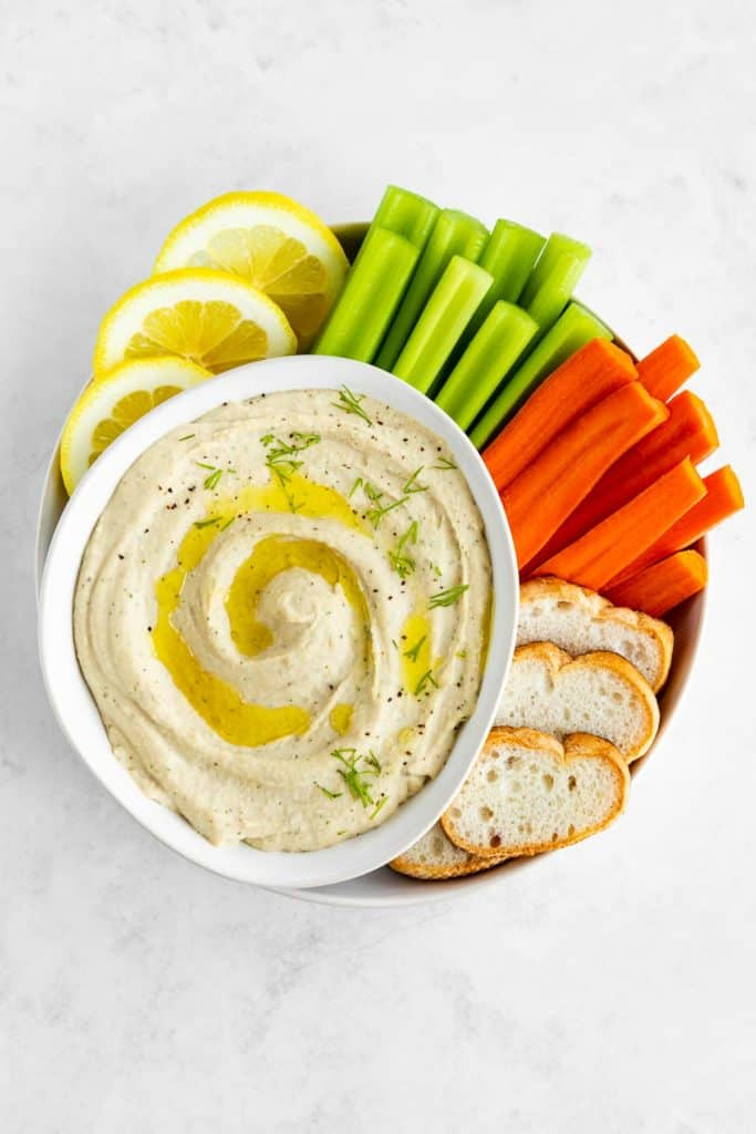 white bean dip inside a bowl surrounded by celery, carrots, bread, and lemon