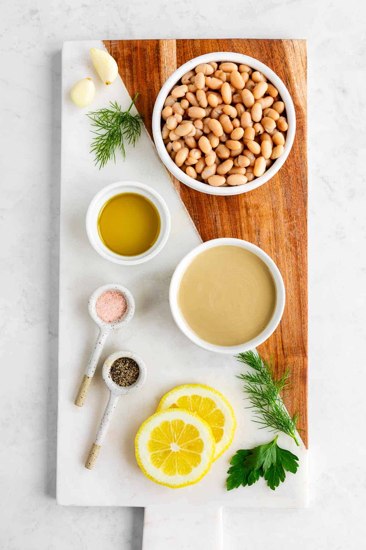 a marble serving board topped with bowls of white beans, tahini, olive oil, a sliced lemon, dill, parsley, and garlic