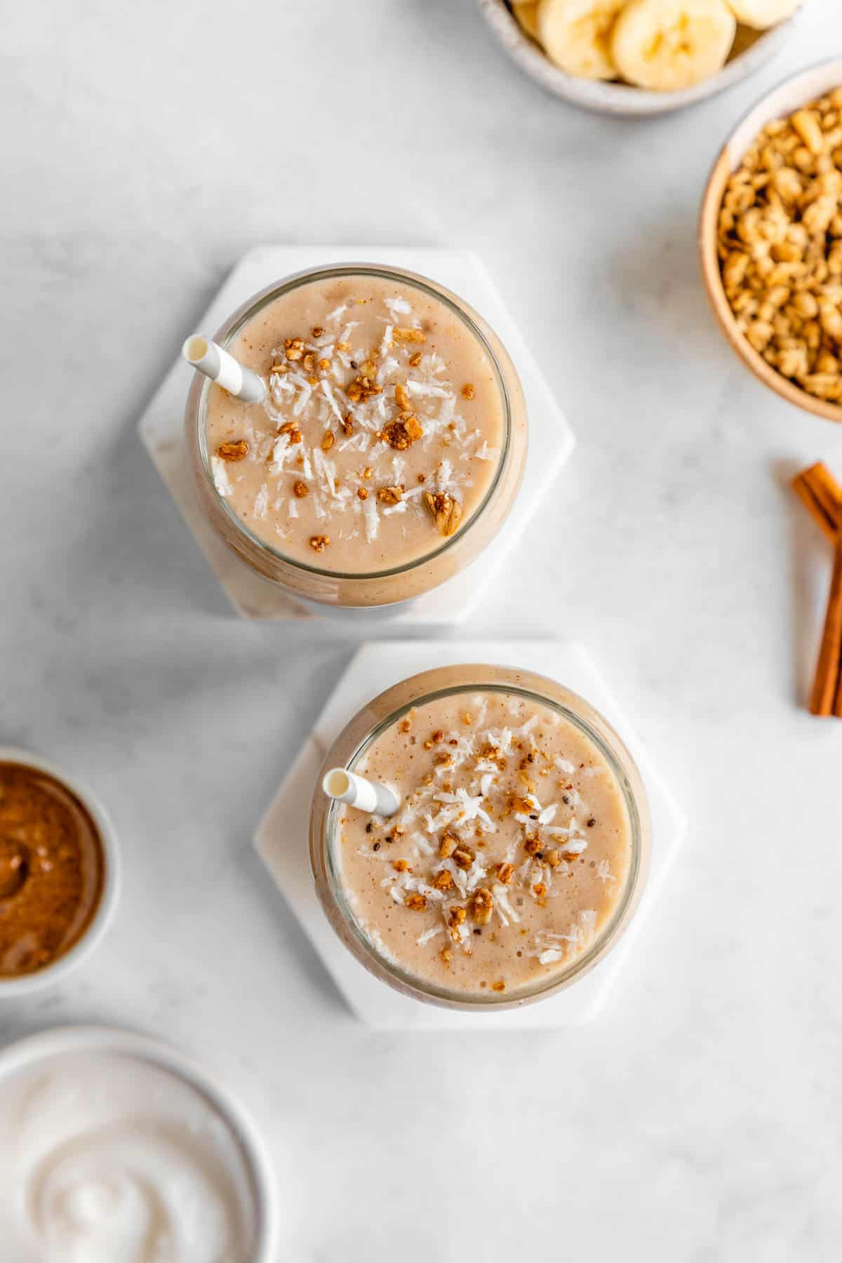 overhead photo of two glasses filled with banana almond butter smoothie