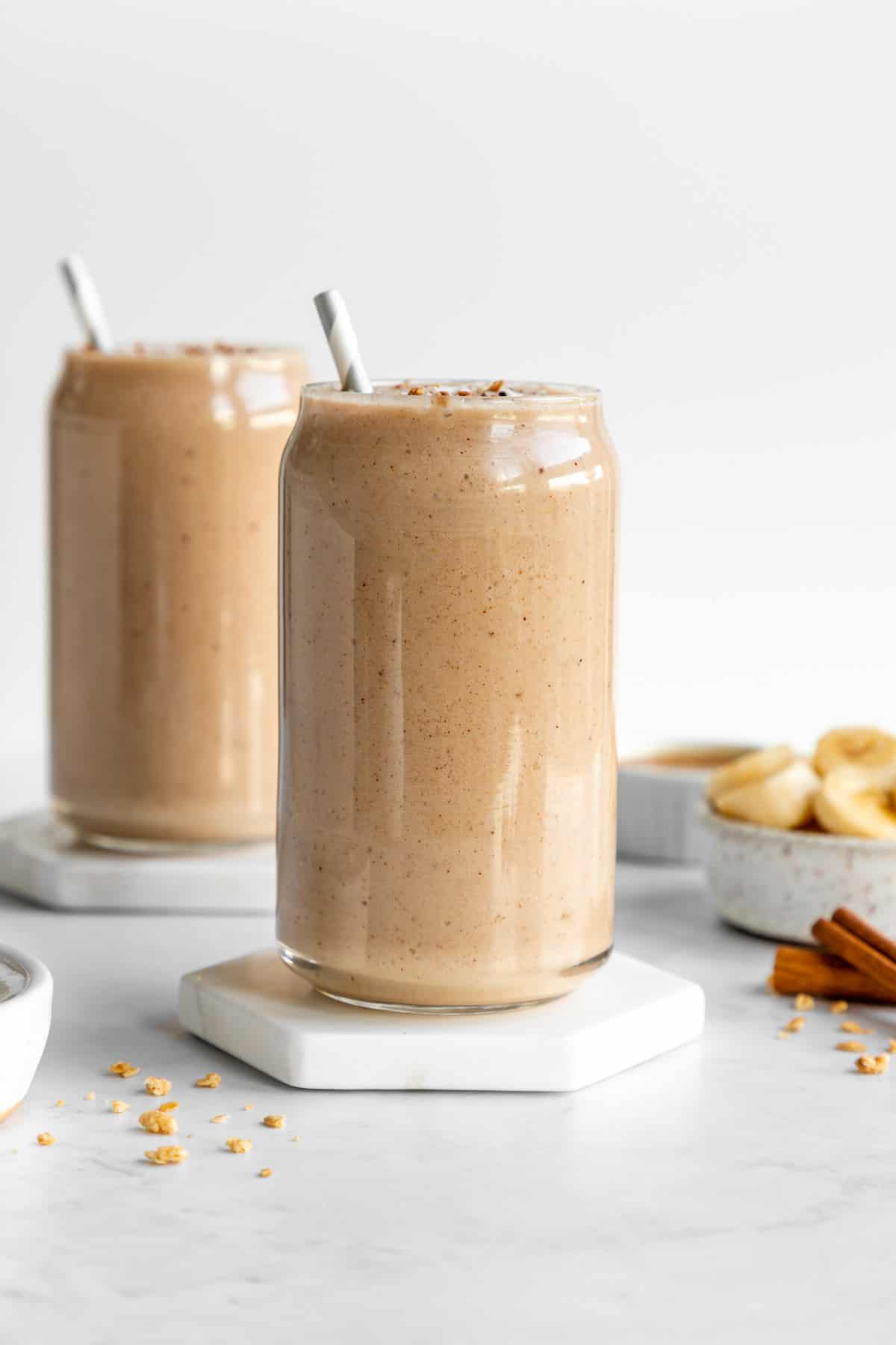 two glasses filled with banana almond butter smoothie