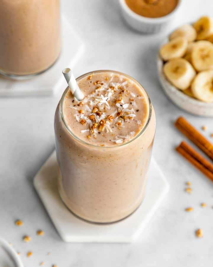 banana almond butter smoothie inside a glass surrounded by ingredients