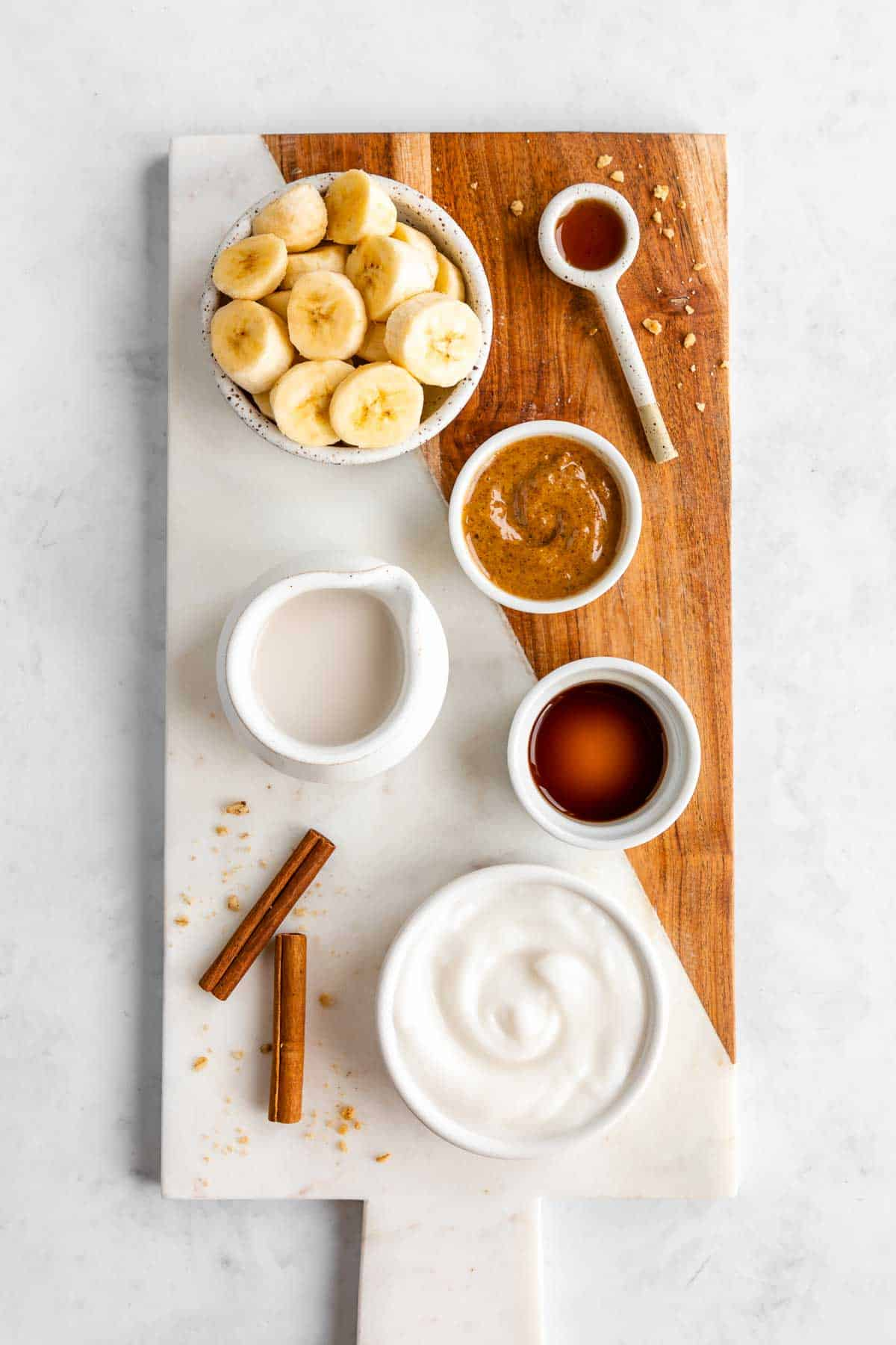 a marble serving board topped with sliced banana, almond butter, almond milk, dairy free yogurt, cinnamon sticks, maple syrup, and vanilla