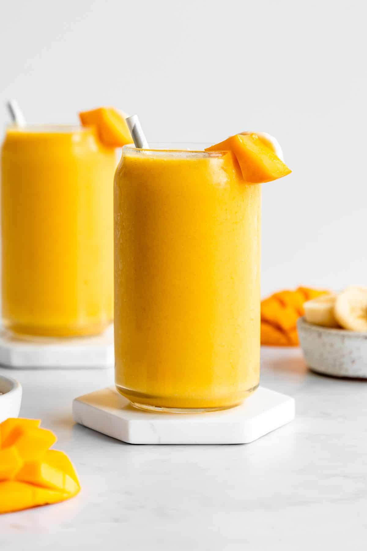 mango banana smoothie inside two glasses