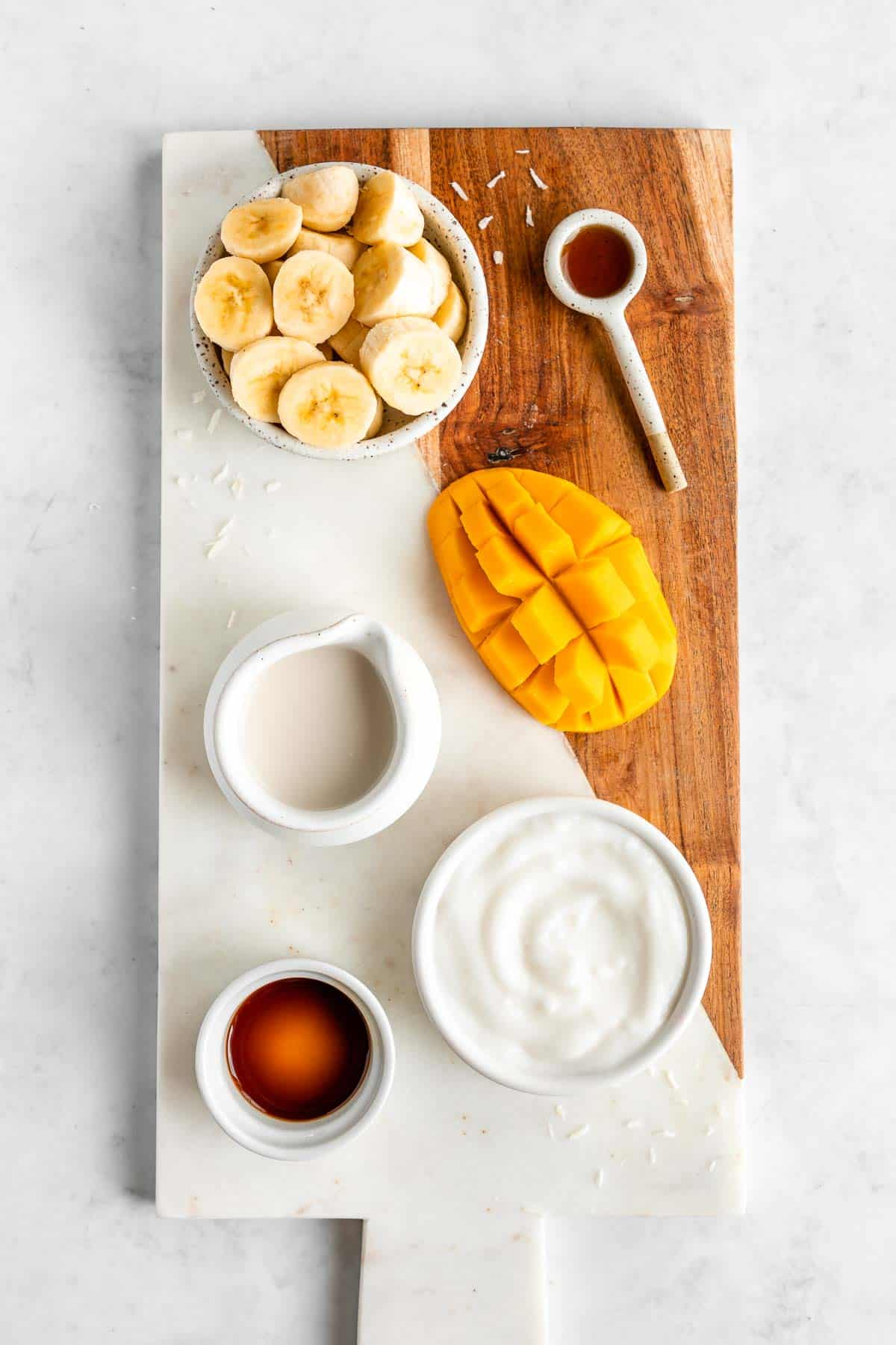 a marble serving board topped with sliced banana, mango, coconut milk, non dairy yogurt, maple syrup, and vanilla extract