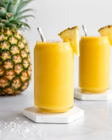 two pineapple coconut smoothies in glasses