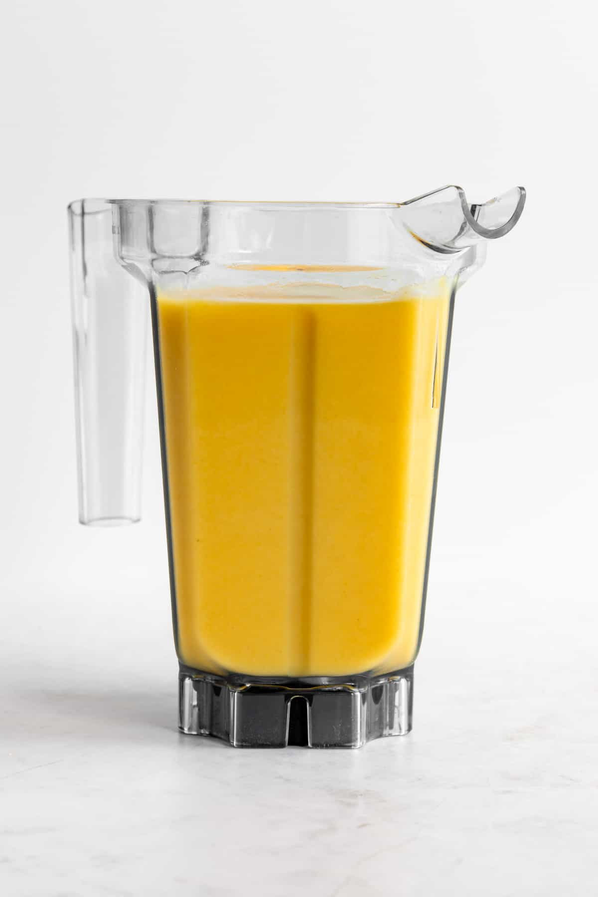 a yellow smoothie inside a vitamix blender