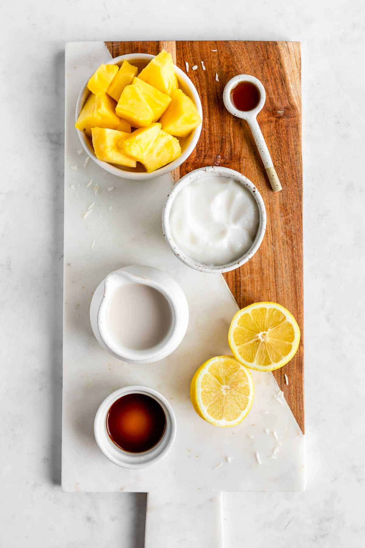 pineapple, coconut yogurt, coconut milk, maple syrup, lemons, and vanilla extract on a marble serving board