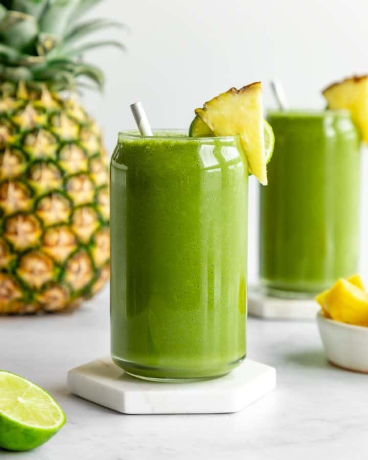 pineapple green smoothie inside two glasses beside a large pineapple