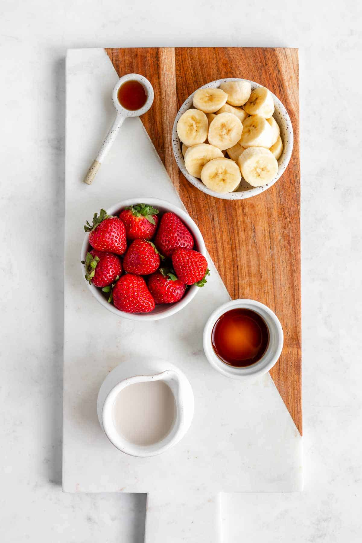 bowls filled with strawberries, banana, vanilla extract, almond milk, and maple syrup on a marble board