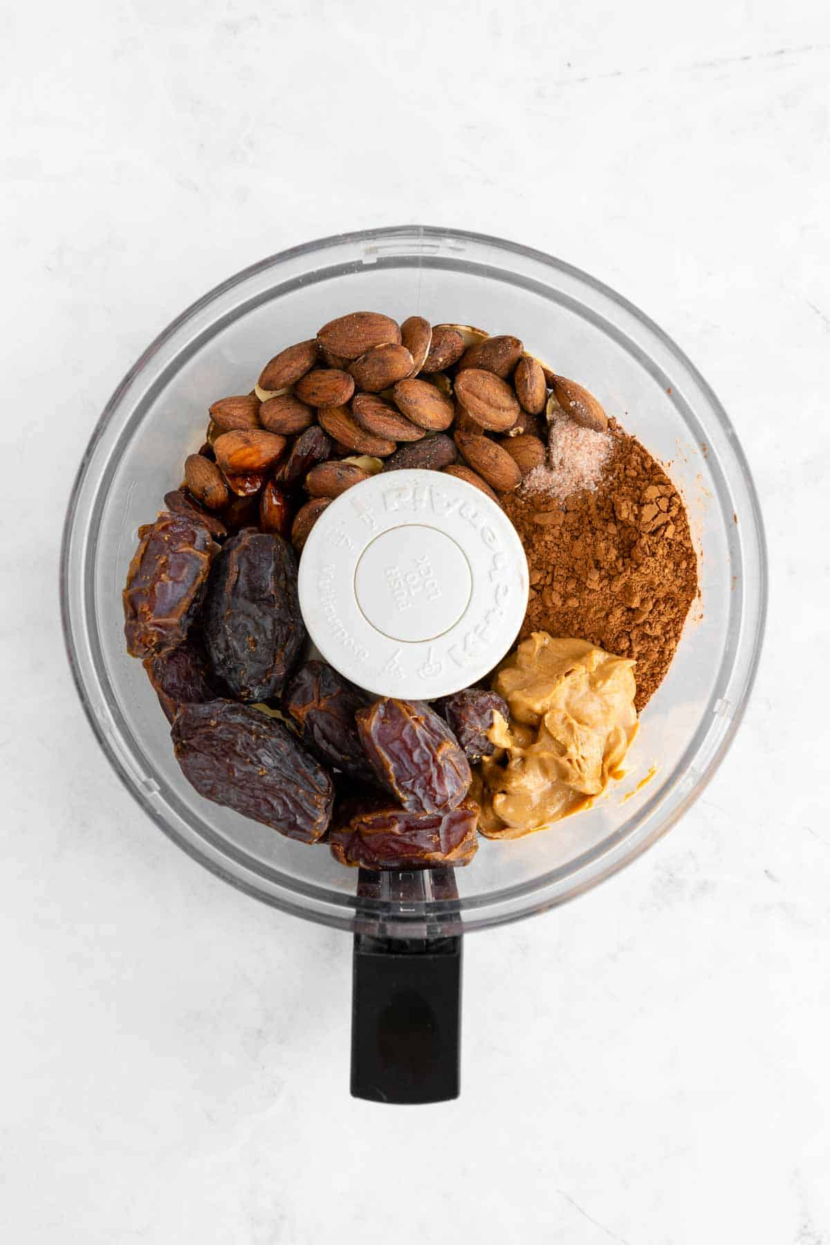 coffee soaked almonds, medjool dates, cocoa powder, almond butter, and salt inside a food processor