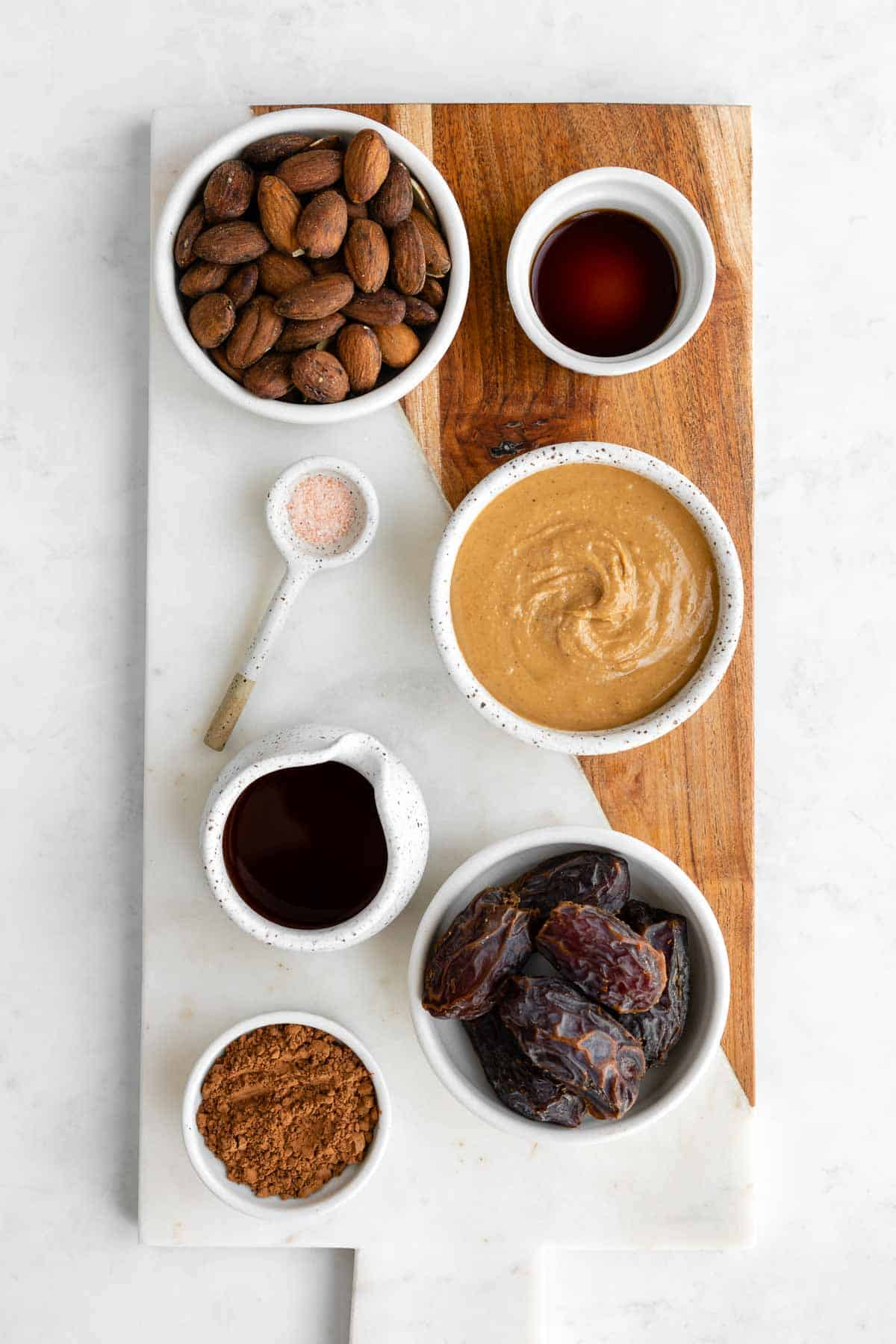 a marble serving board topped with bowls of coffee soaked almonds, medjool dates, almond butter, maple syrup, cocoa powder, vanilla extract, and salt