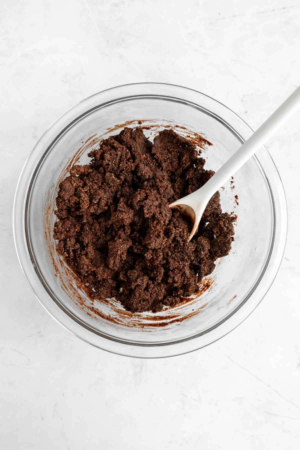 mixing raw brownie dough in a glass bowl