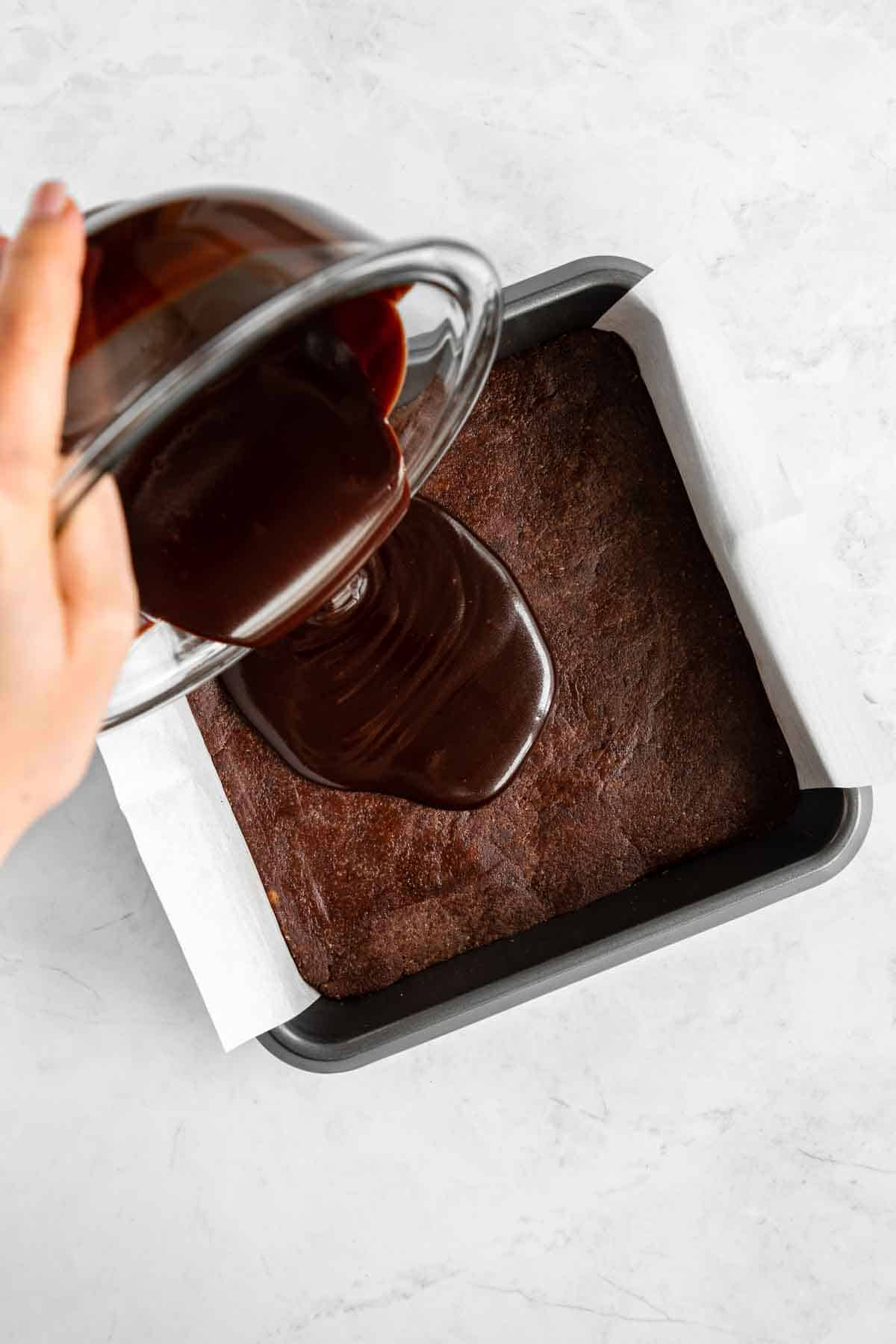 pouring chocolate ganache over no bake brownies in a square pan