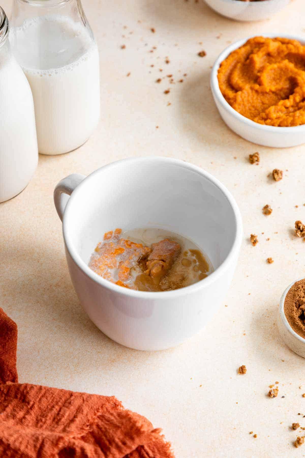 pumpkin puree, oat flour, almond milk, and almond butter in a white mug