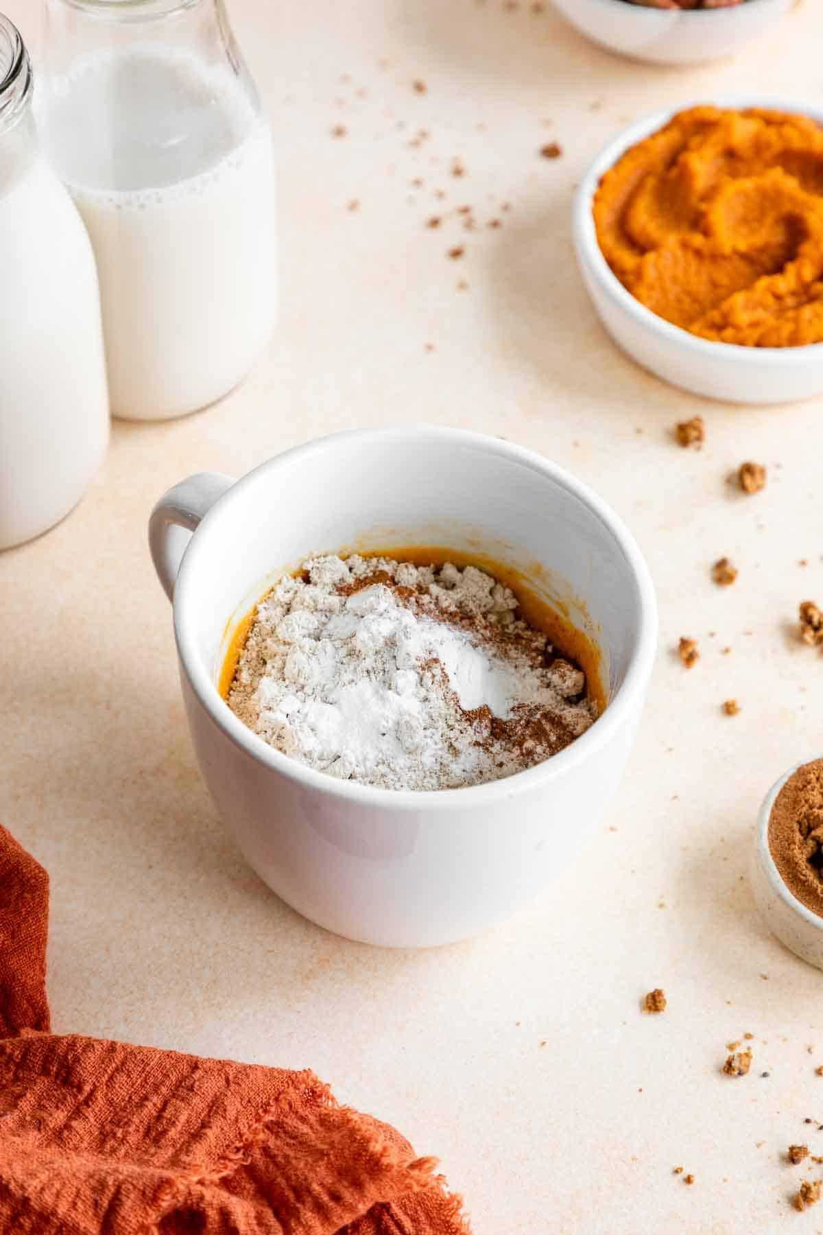 oat flour and pumpkin cake batter in a white mug
