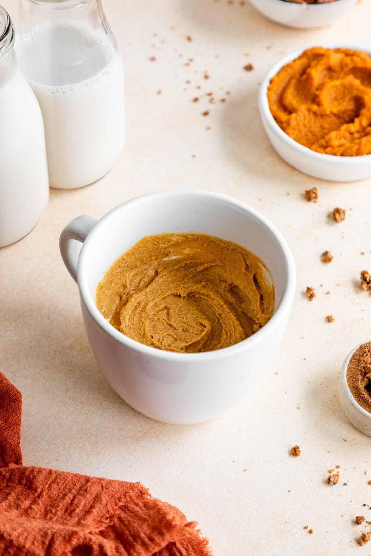 vegan gluten-free pumpkin cake batter inside a white mug