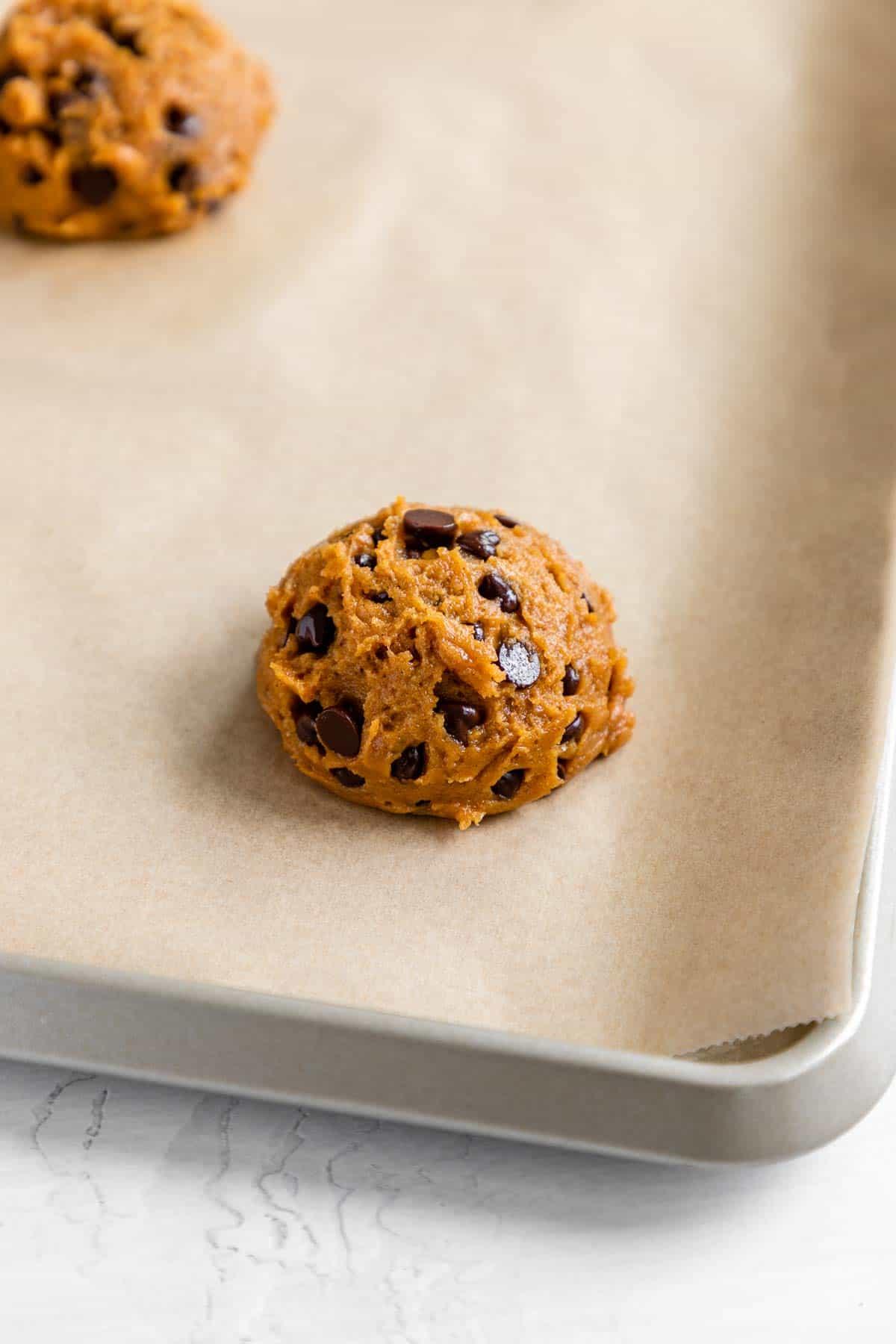 a round of vegan pumpkin chocolate chip cookie dough on a baking sheet