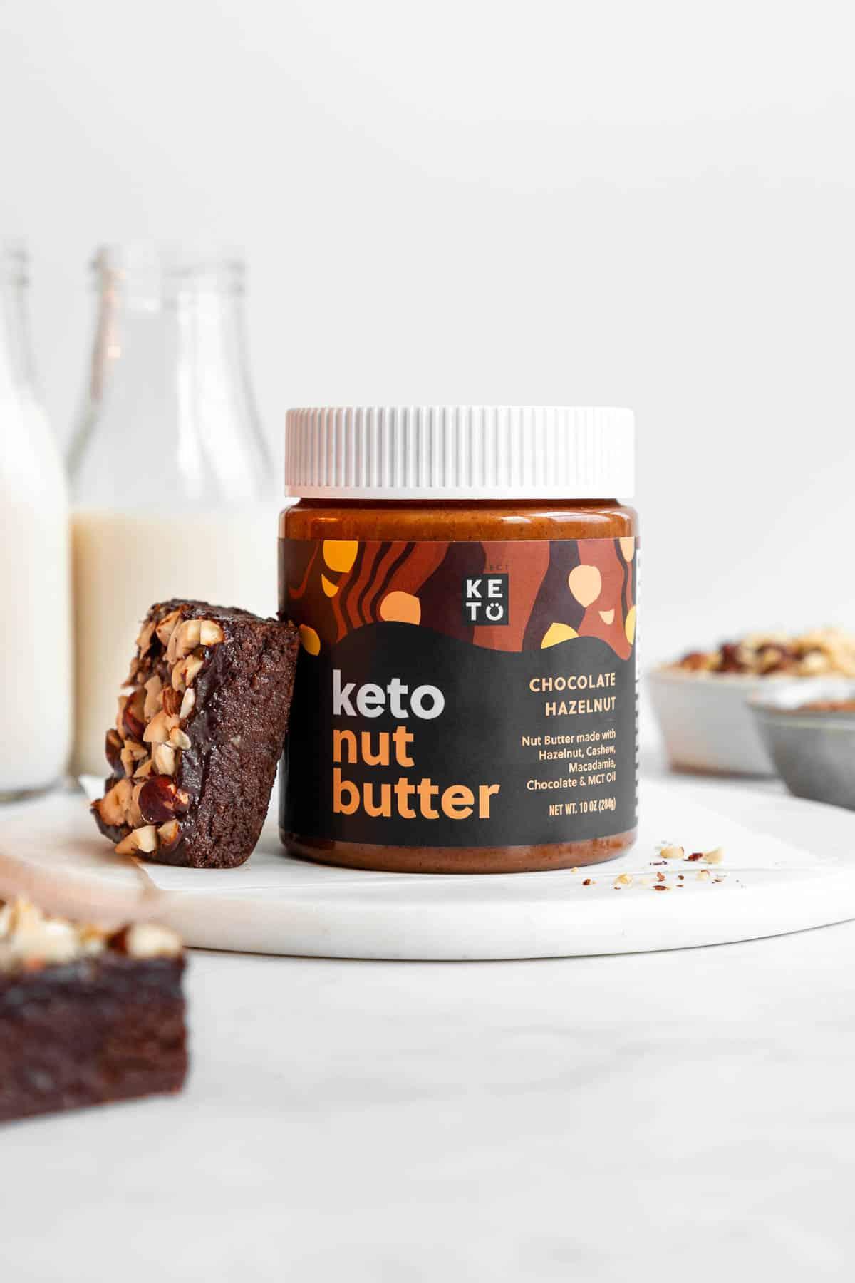 perfect keto chocolate hazelnut butter beside a no-bake brownie
