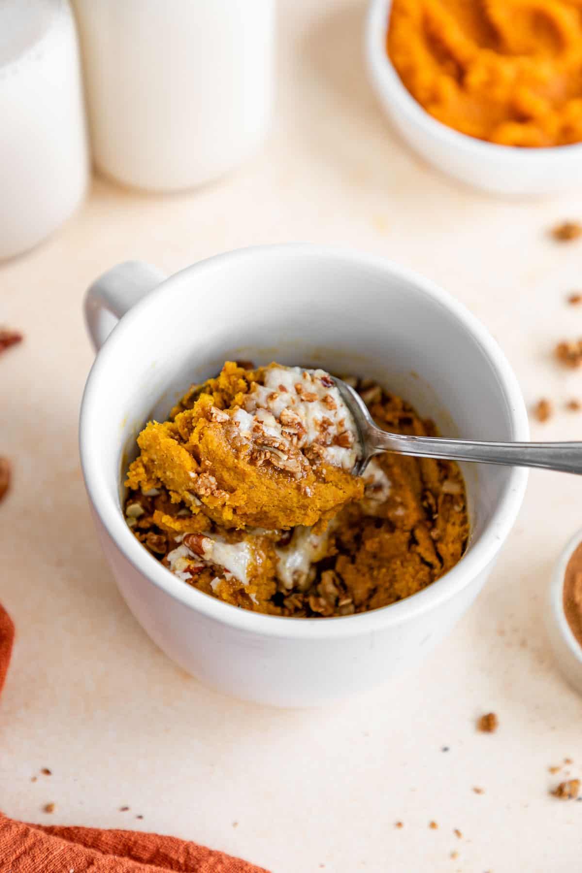 a spoon scooping a bite of vegan pumpkin mug cake out of a white mug