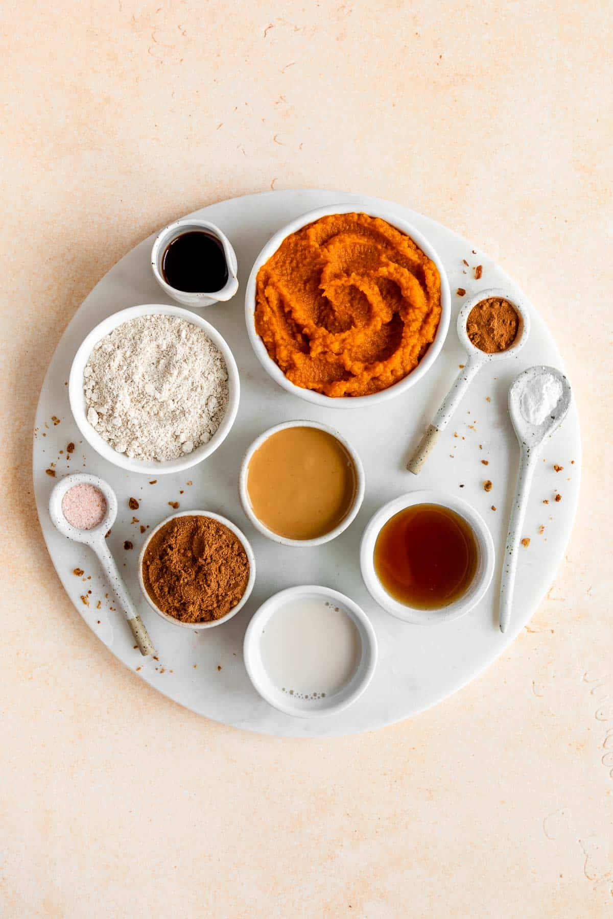 a round marble board with bowls of pumpkin puree, oat flour, almond butter, almond milk, maple syrup, cinnamon, and vanilla